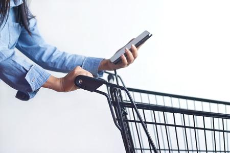 Foto de Closeup of woman with shopping cart and shopping list in smartphone in hand - Imagen libre de derechos