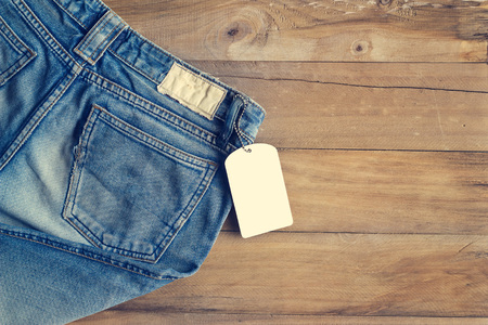 Photo for Blue jeans with white blank tag on wooden background - Royalty Free Image