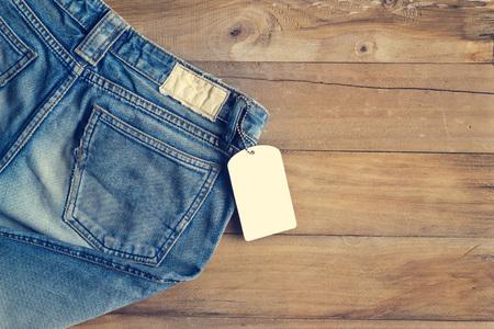 Foto de Blue jeans with white blank tag on wooden background - Imagen libre de derechos