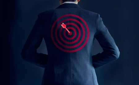 Foto de businessman get success with red arrow on target at the back of his suit on dark background, business concept - Imagen libre de derechos