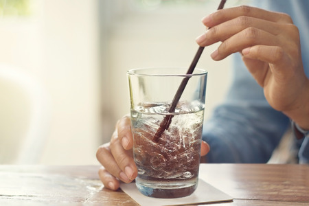Foto de glass of water and ice in hands on table restaurant background - Imagen libre de derechos