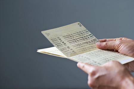 Photo pour hands holding saving account passbook, book bank on gray background - image libre de droit
