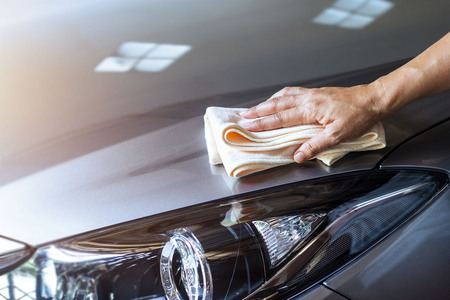 Foto de woman cleaning car with microfiber cloth and clean spray - Imagen libre de derechos