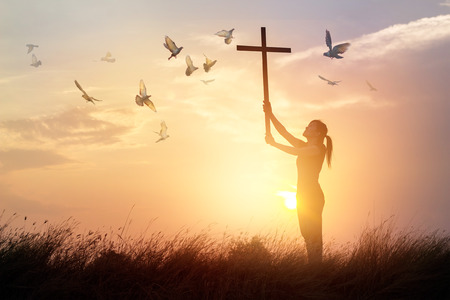 Foto de Woman praying with cross and flying bird in nature sunset background, hope concept - Imagen libre de derechos