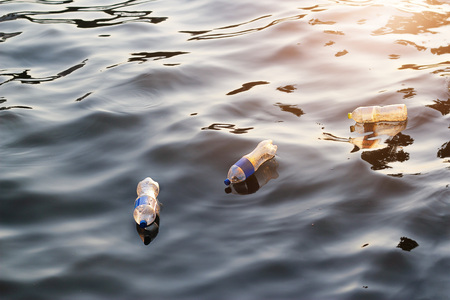Photo pour Plastic garbage in the river on sunset, pollution and environment concept - image libre de droit
