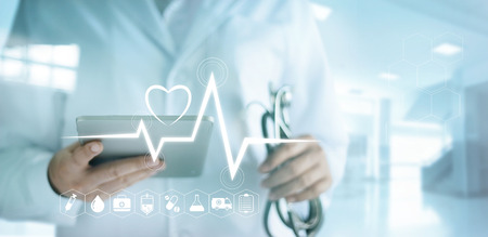 Photo pour Doctor using digital tablet with medical icon and heartbeat rate in the hospital background - image libre de droit