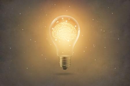 Foto de golden brain glowing inside of light bulb on paper texture background - Imagen libre de derechos