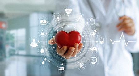 Foto de Medicine doctor holding red heart shape in hand and icon medical network connection with modern virtual screen interface, medical technology network concept - Imagen libre de derechos