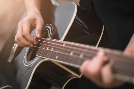 Photo pour Guitar player playing acoustic guitar, close up - image libre de droit