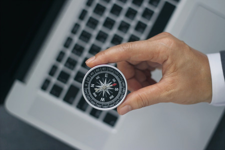 Businessman with a compass holding in hand on laptop background