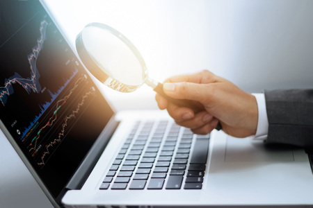 Foto de Businessman holding magnifying glass in hand ,search of stock market data on laptop screen, investment trading concept - Imagen libre de derechos