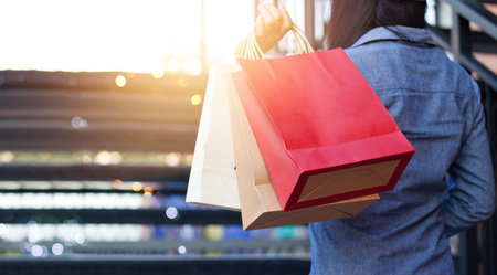 Photo pour Rear view of woman holding shopping bag while up stairs outdoors on the mall background - image libre de droit