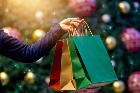 Foto für Christmas shopping bags in hand on christmas decoration and light at night on street background - Lizenzfreies Bild