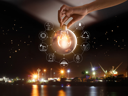 Foto de Hand holding light bulb in front of global show the world's consumption with icons energy sources for renewable, sustainable development. Ecology concept. Elements of this image furnished by NASA. - Imagen libre de derechos