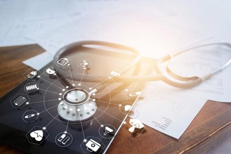 Foto de Stethoscope with icon medical on tablet and wooden table backgrpund - Imagen libre de derechos