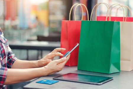 Foto für Online shopping. Woman using smartphone with credit card. Mobile phone, Website on ipad and shopping bags on table, department store background. Consumer commerce concept. - Lizenzfreies Bild