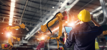 Foto de Engineer using tablet check and control automation robot arms machine in intelligent factory industrial on monitoring system software. Welding robotics and digital manufacturing operation. - Imagen libre de derechos