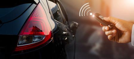 Foto de Close up businessman hand pressing car key remote control to unlock with sign icon - Imagen libre de derechos