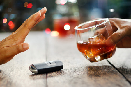 Foto de Man hand with car key on table rejecting glass with alcoholic beverage on colorful background - Imagen libre de derechos