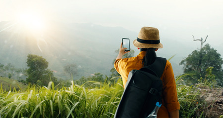 Foto de backpack using smartphone taking picture beautiful landscape on mountain peak while exploring, trekking in tropical rain forest of Asia - Imagen libre de derechos