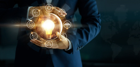 Photo pour Businessman' s hand holding glowing light bulb with energy sources icon. Campaigning for ecological friendly and sustainable environment. Earth day. Energy saving concept - image libre de droit
