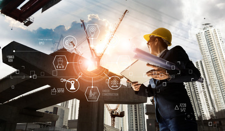 Foto de A futuristic architect, Businessman, Industry 4.0. Engineer manager using tablet with icon network connection in construction site, Industrial and innovation. Industry technology concept. - Imagen libre de derechos
