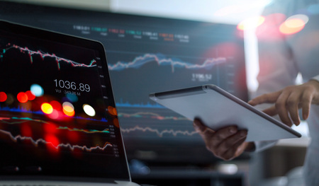Foto de Businessman using tablet and laptop for analyzing data stock market in monitoring room background, forex trading graph, stock exchange trading online, financial investment concept. All on laptop screen are design up. - Imagen libre de derechos