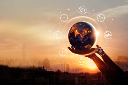 Photo pour Earth at night was holding in human hands with energy resources icon on city background. Earth day. Energy saving concept. - image libre de droit