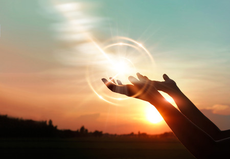 Foto de Woman hands praying for blessing from god on sunset background - Imagen libre de derechos