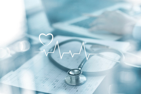 Foto de Stethoscope with heart beat report and doctor analyzing checkup on laptop in health medical laboratory background - Imagen libre de derechos