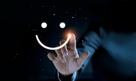 Photo pour Finger of businessman touching and drawing face emoticon smile on dark background, service mind, service rating. Satisfaction and  customer service concept. - image libre de droit