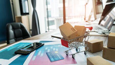 Foto de E-commerce. Paper boxes in shopping cart and credit card with smartphone on sales data economic growth graph - Imagen libre de derechos