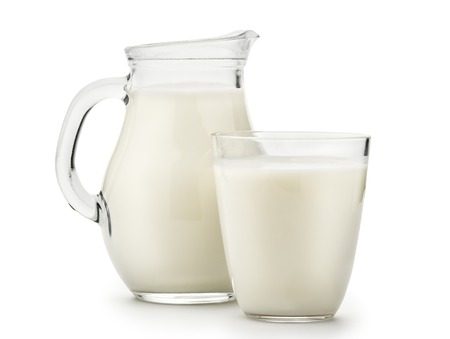 Foto de Natural whole milk in a jug and a glass isolated on a white background closeup - Imagen libre de derechos