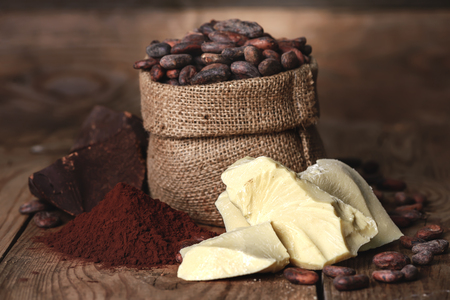 Photo for Cocoa butter and ingredients for making chocolate, Cocoa powder in the bowl, cocoa beans on old wooden background - Royalty Free Image