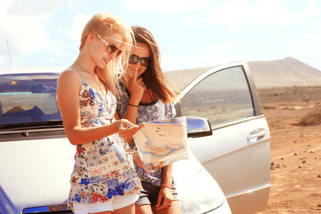 Photo pour Two young women with car look at road map with mountain landscape in background - image libre de droit