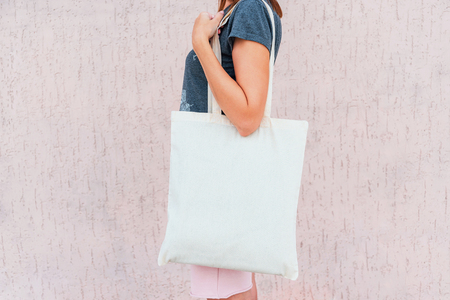 Photo pour Young woman with white cotton bag in her hands. Mock up. - image libre de droit