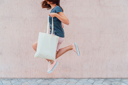 Foto de Young woman is jumping with white cotton bag in her hands. Mock up. - Imagen libre de derechos