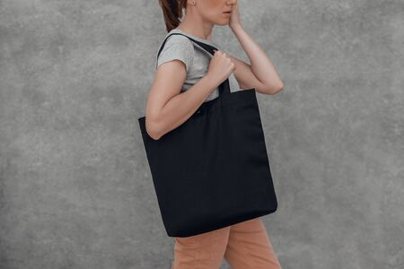 Photo pour Young woman with black cotton bag in her hands on grey background. Cropped. - image libre de droit