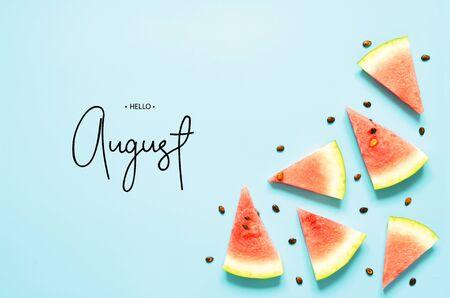 Foto de Inscription Hello August. Fresh red watermelon slice Isolated light blue background. Top view, Flat lay. - Image - Imagen libre de derechos