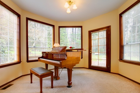 Round room with piano and lots of windows.