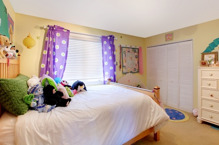 Yelow baby room with purple curtains and yellow walls.