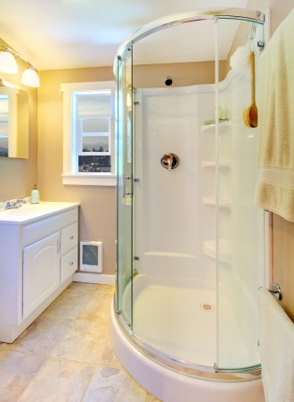Small beige bathroom with walk in white shower and white cabinet.