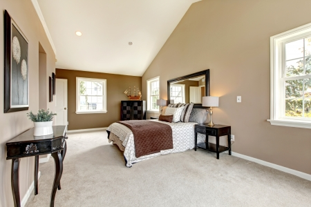 Large classic luxury bedroom with brown and white and beige carpet.