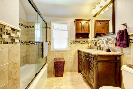 Classic bathroom with natural stone tiles and wood cabinet.