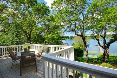 Large balcony home exterior with table and chairs, lake view.