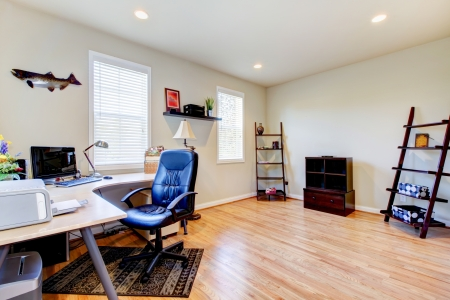 Home office interior with hardwood floor and simple furniture.