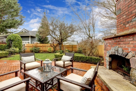 Photo pour Spring fenced luxury  backyard with outdoor fireplace and furniture. - image libre de droit