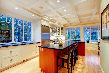 White large luxury kitchen with huge wood island and refrigerator.