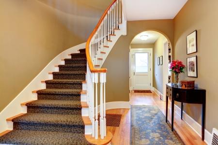 Foto de Warm colors hallway with wood stairs, rustic black cabinet and blue rug - Imagen libre de derechos