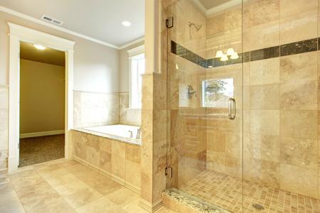 Photo pour Beight and white bathroom with white tub, beige tile floor, glass door shower - image libre de droit